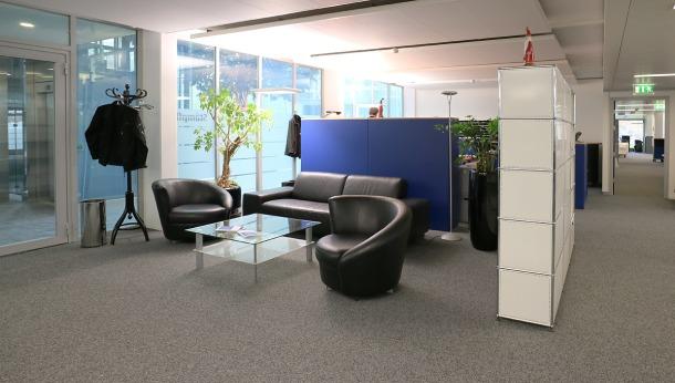 Eingangsbereich mit Polstergruppe, Glastisch und USM-Regal.