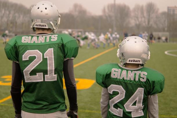 Grosser und kleiner Footballspieler in Shirt mit Aufschrift GIANTS